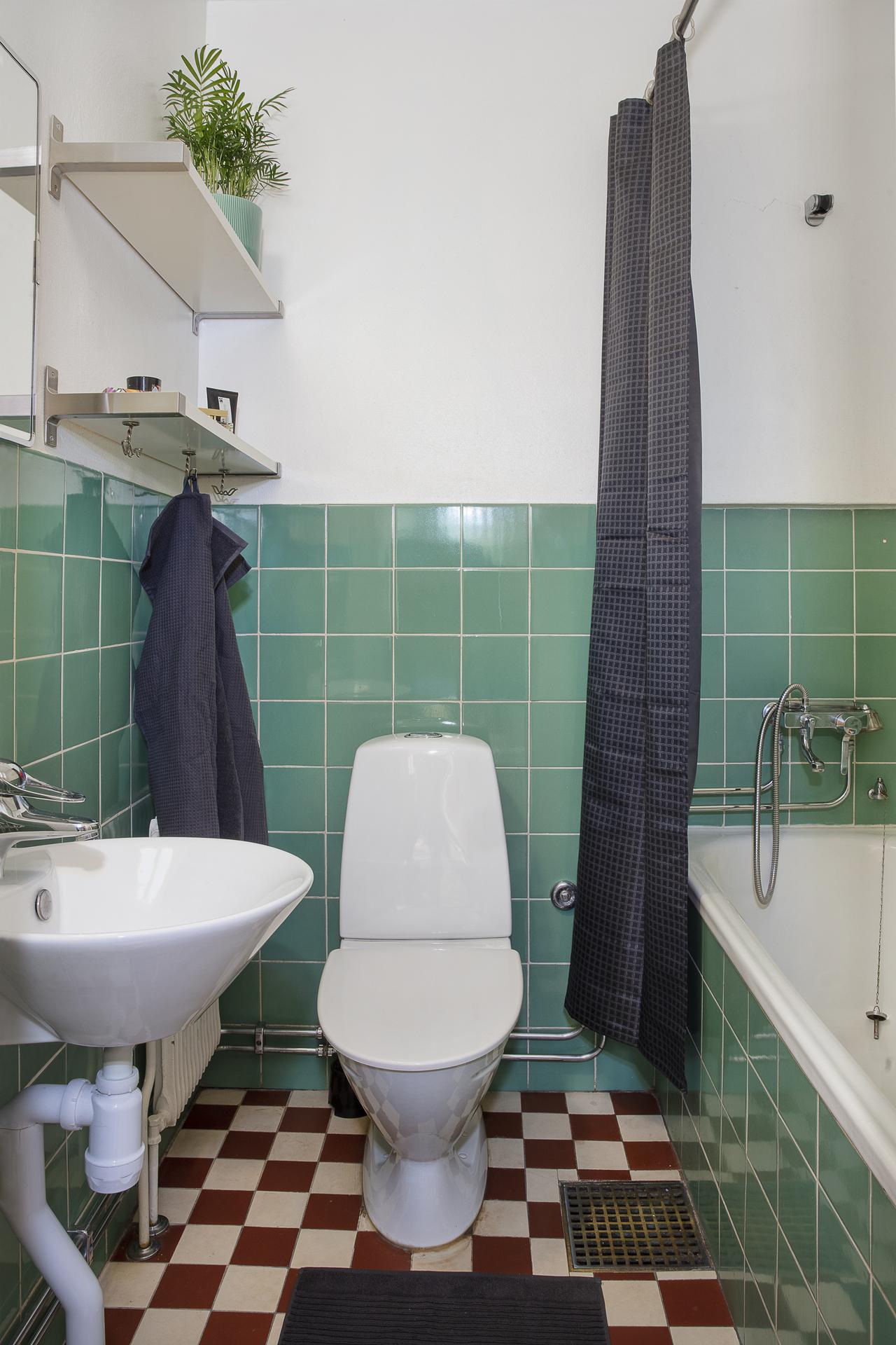 Badrummet som är i originalutförande har ett inkaklat badkar