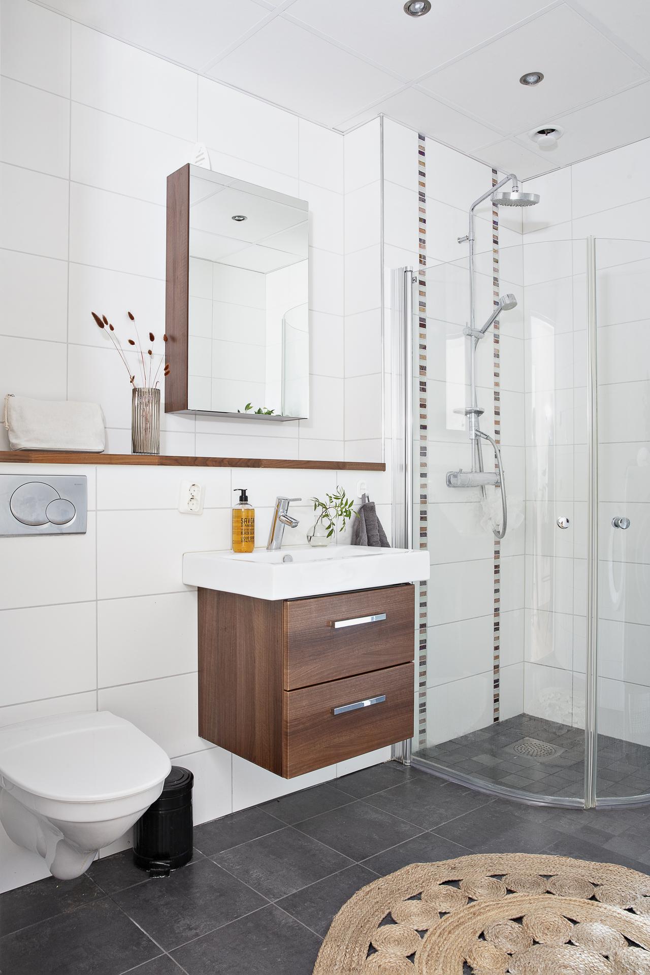 Det helkaklade badrummet har bra med plats för förvaring i både kommod och spegelskåp