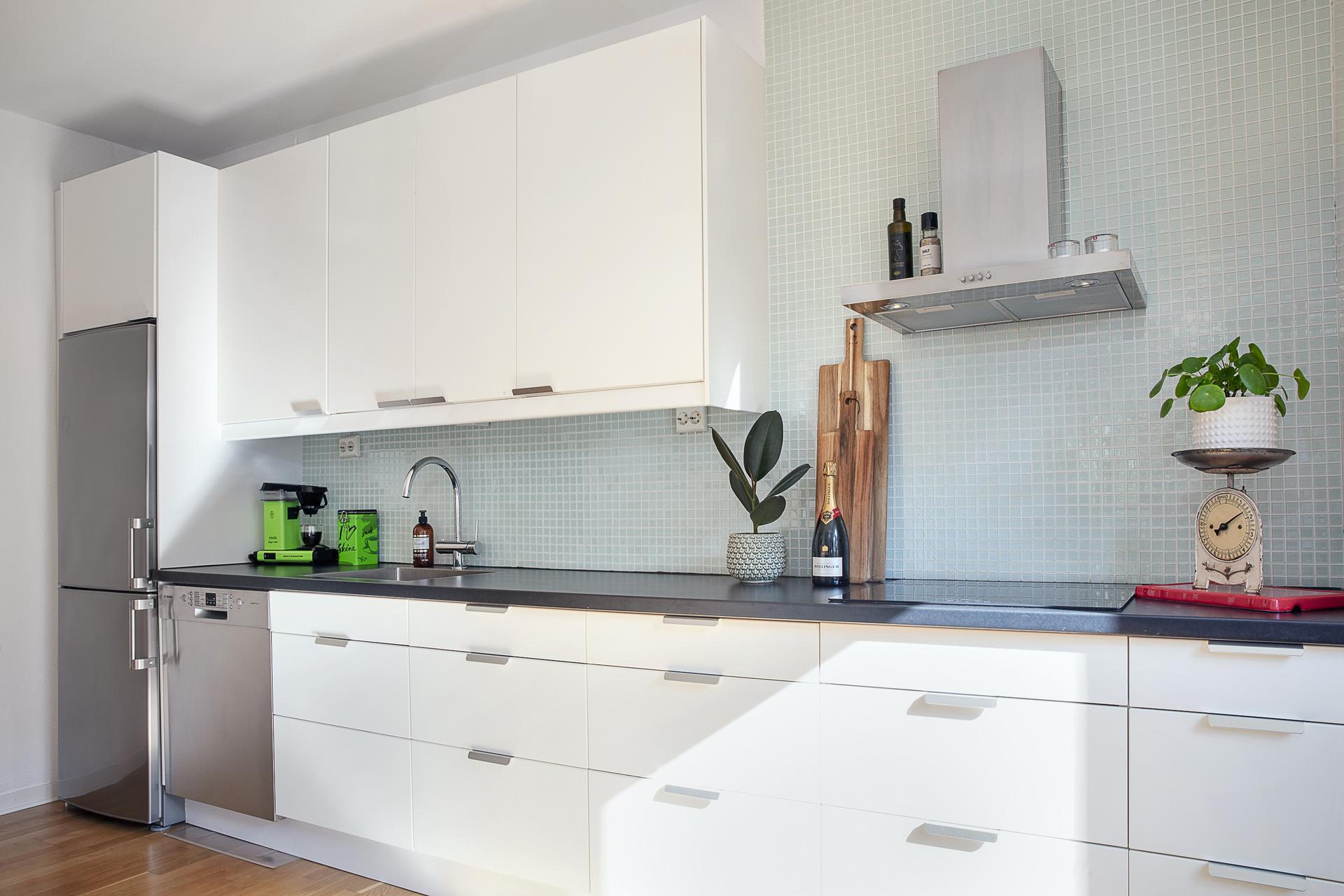 Köket erbjuder vita släta luckor samt gott om plats för förvaring