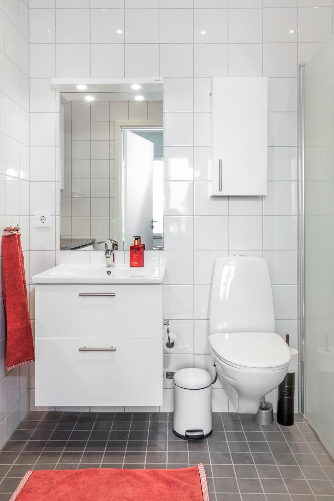 Badrummet, som nås ifrån sovrum 2, är helkaklat i vitt och grått