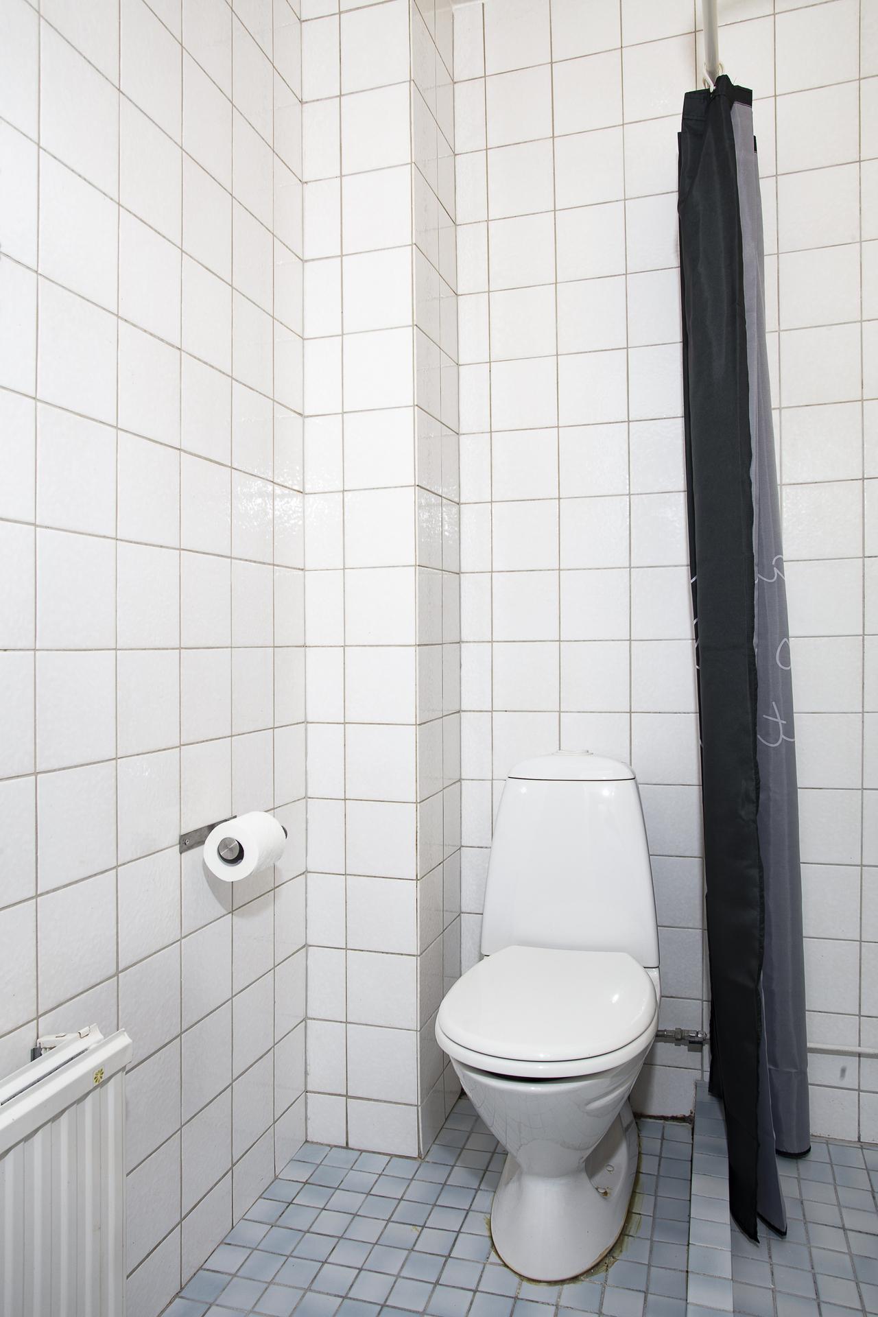 Badrum 2 är helkaklat med vitt kakel samt blått klinkers på golvet