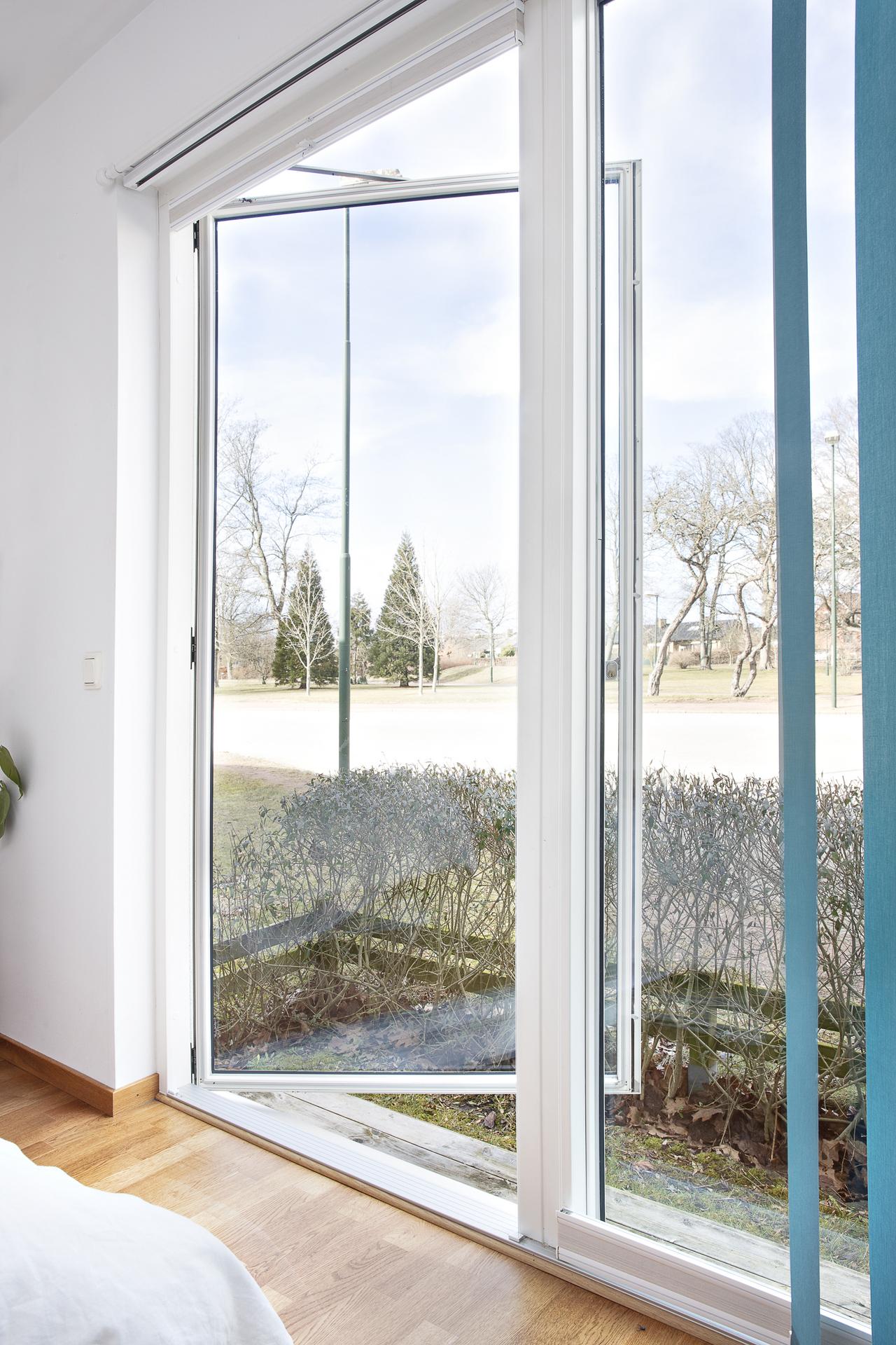 Fönster med både lamellgardiner och plisségardiner samt utgång till uteplats på baksidan