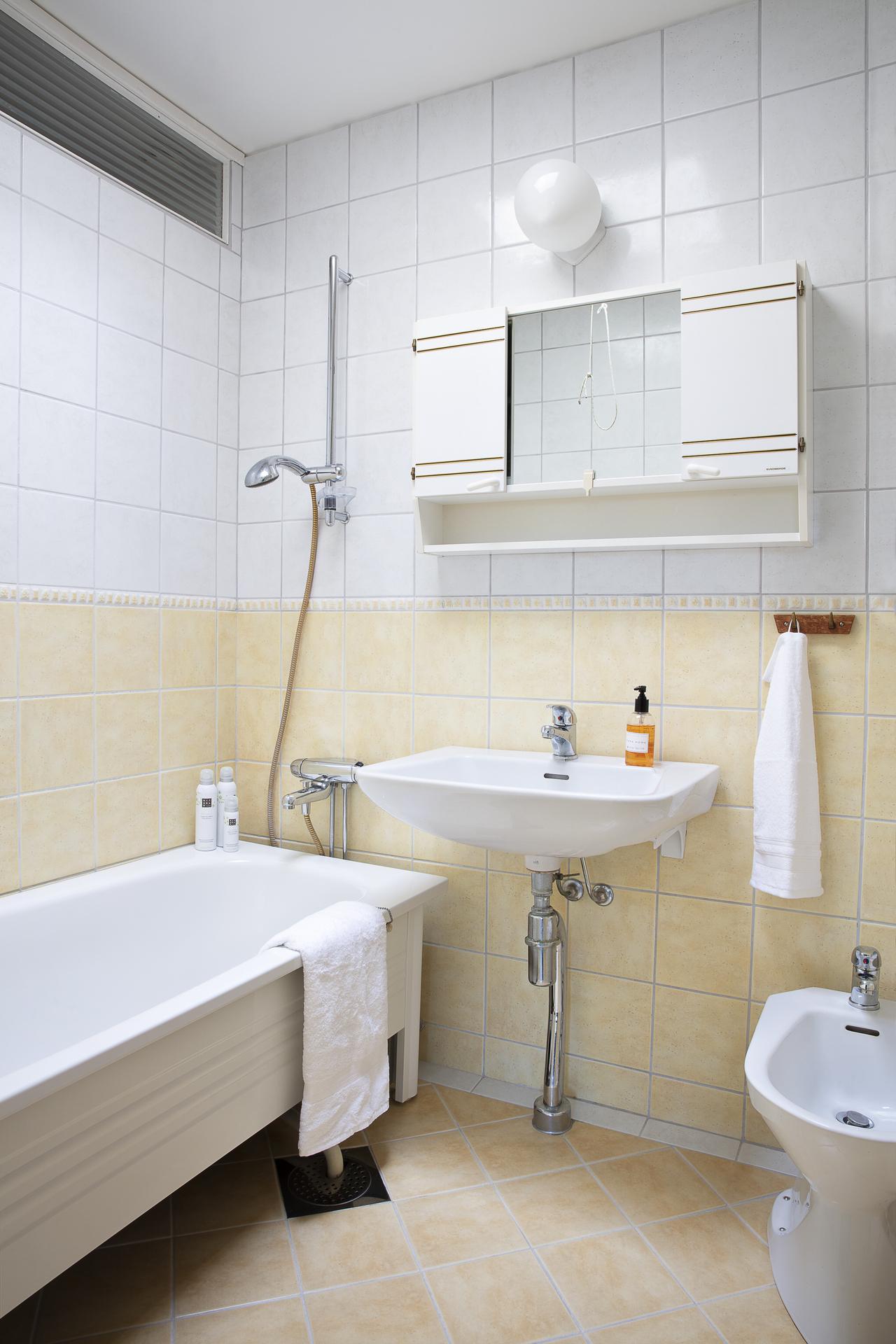 Här finns ett fristående badkar och badrumsskåp med plats för förvaring