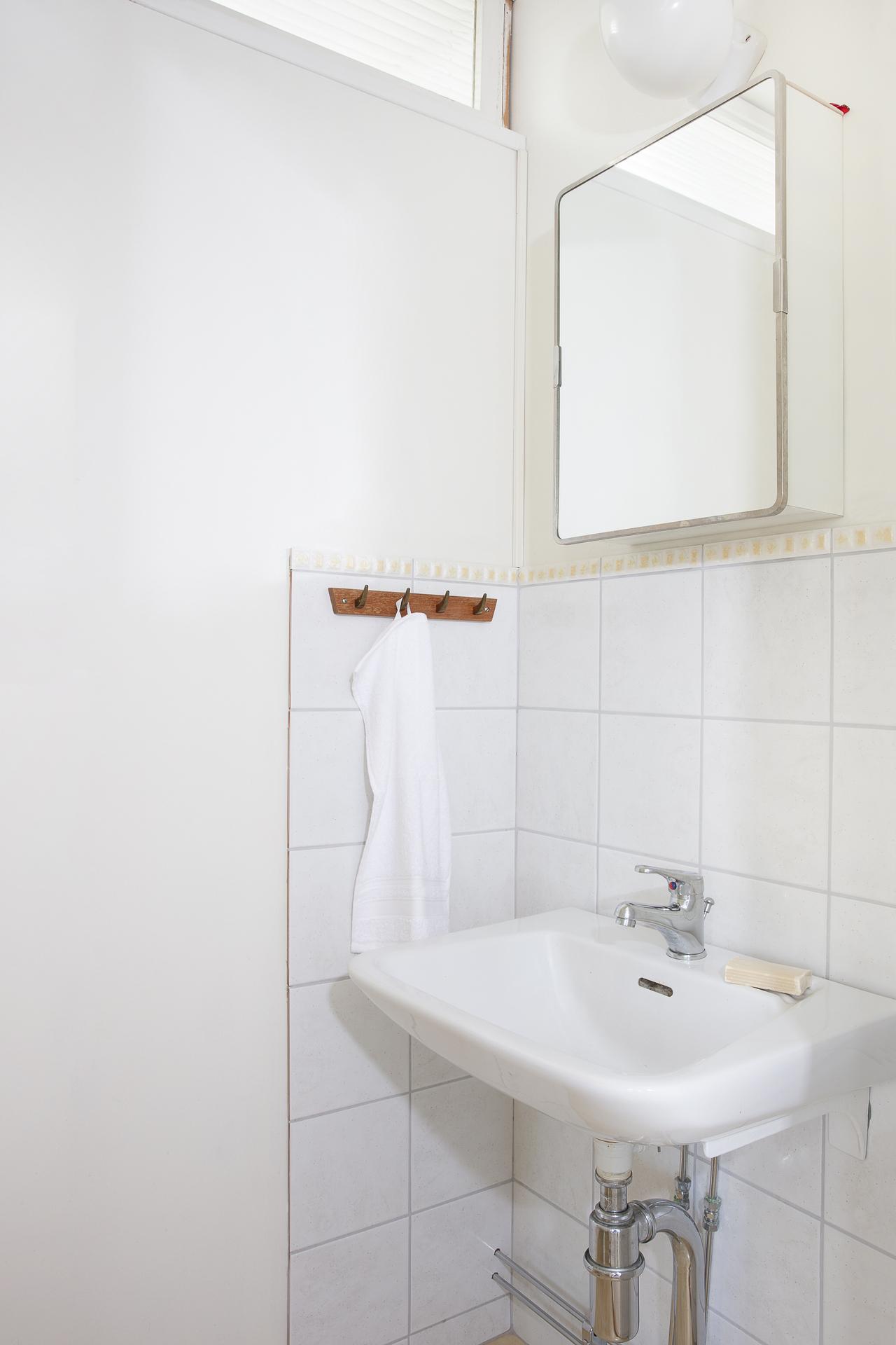 Här finns vask med spegelskåp till förvaring
