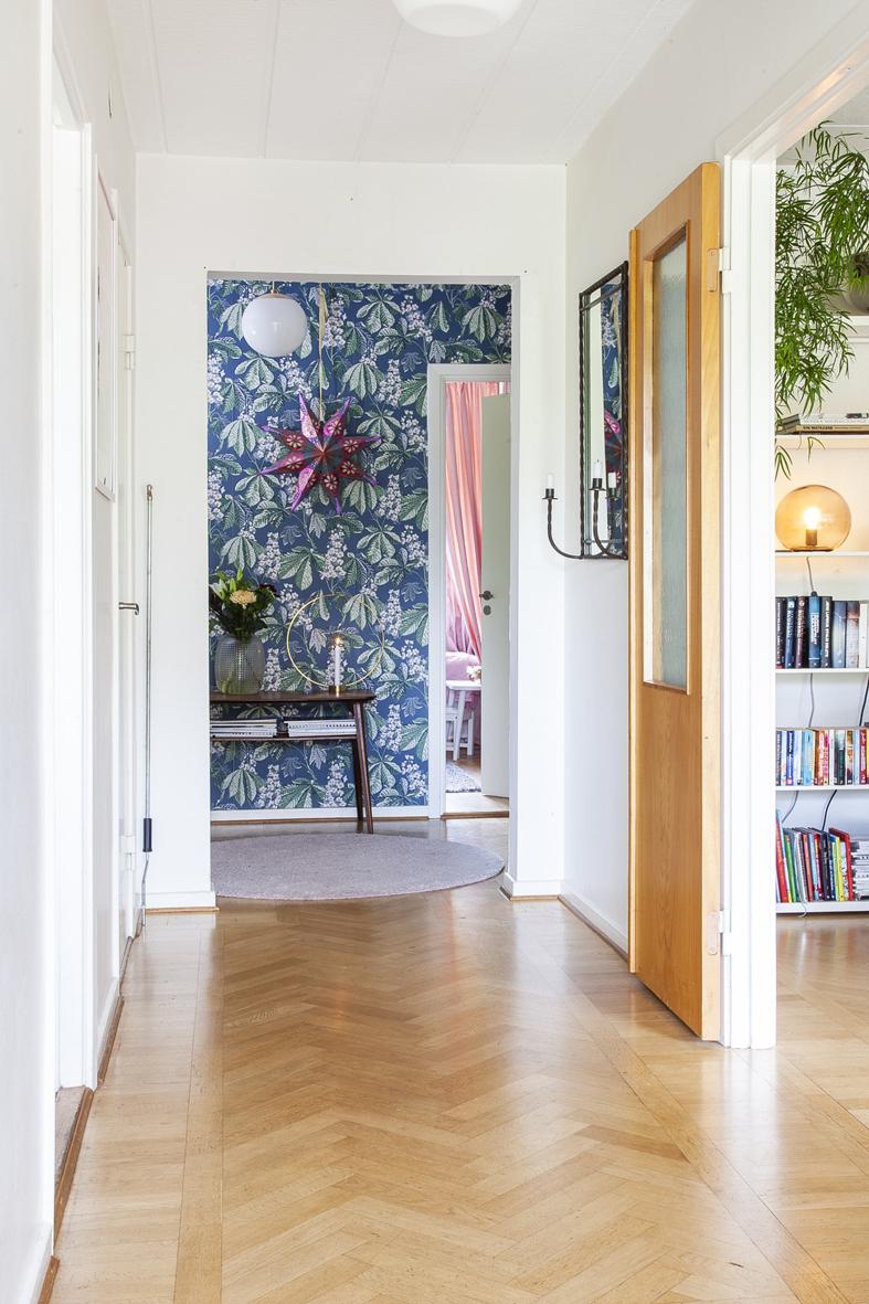 Hall  med fiskbensparkett på golvet och vitmålade väggar