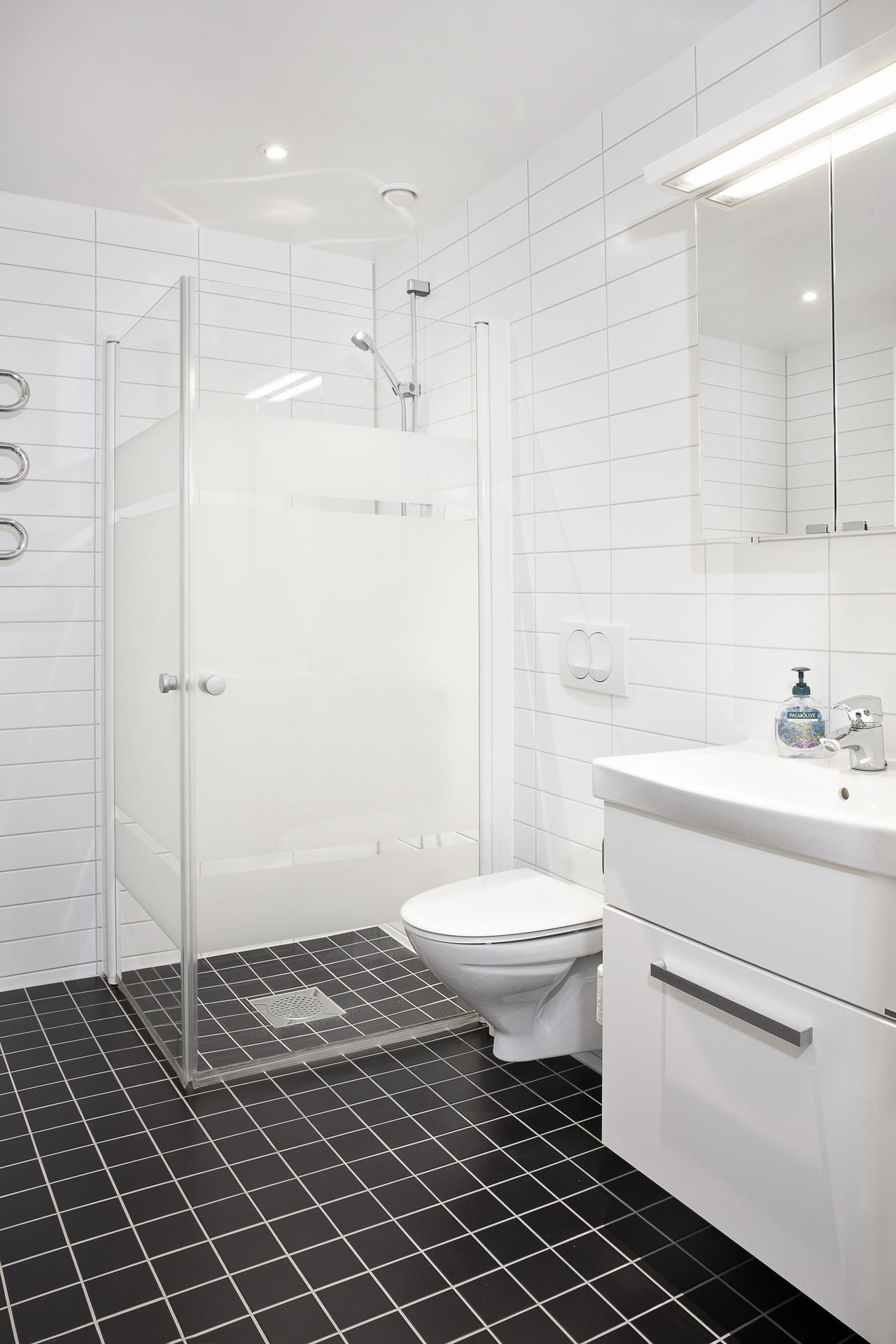 Det helkaklade badrummet erbjuder dusch bakom vikbara duschväggar