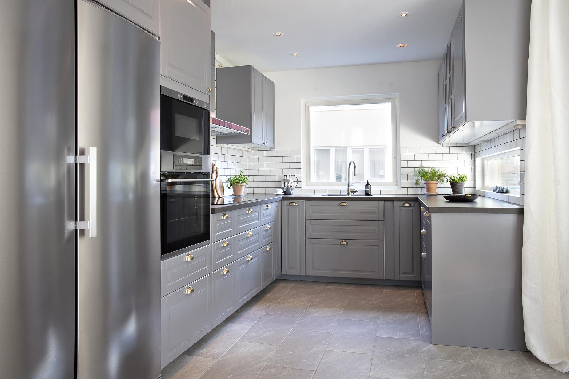 Det är ett stilrent kök som går i gråa toner med fönster ut mot gården i söder