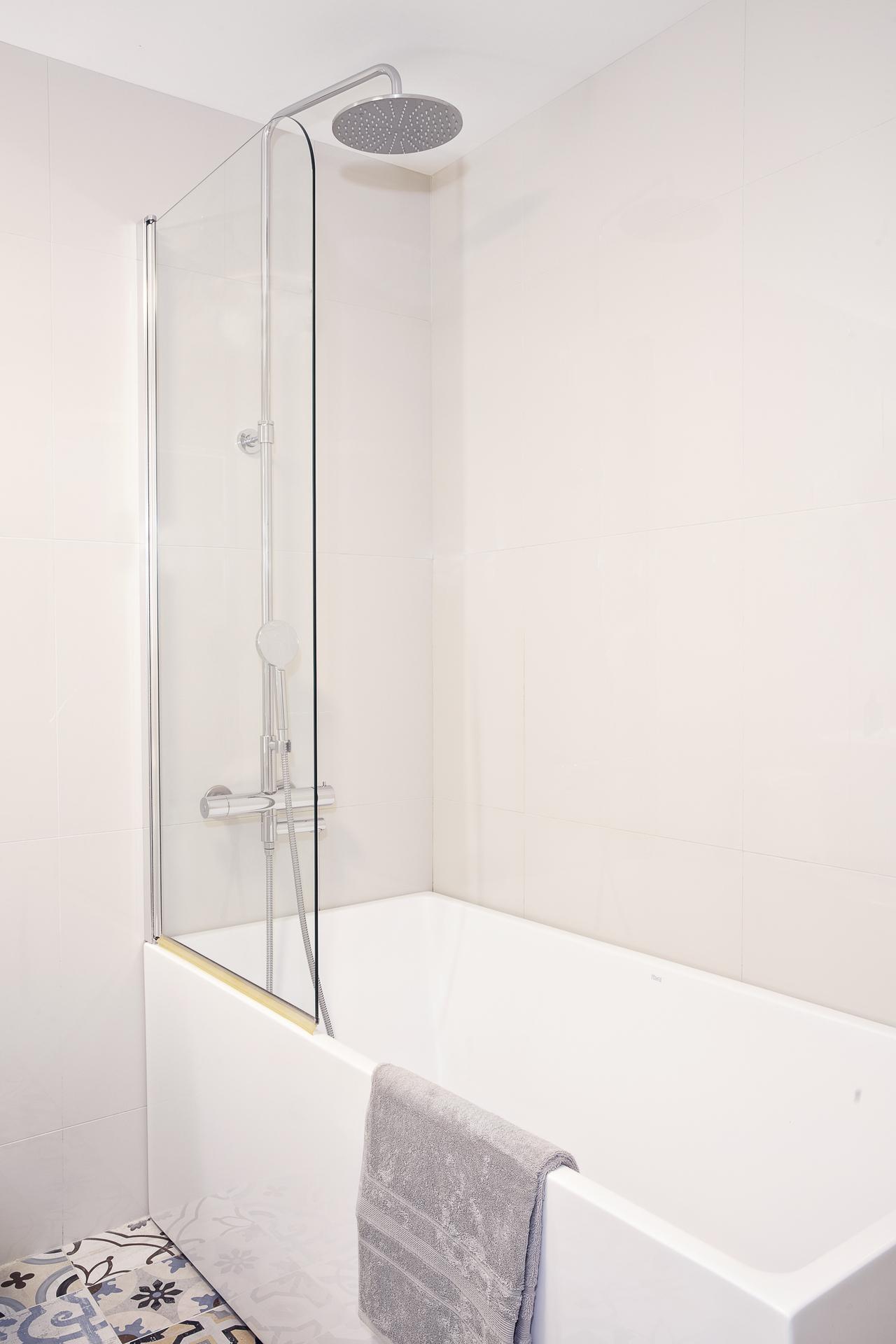 Här finns ett badkar med duschvägg