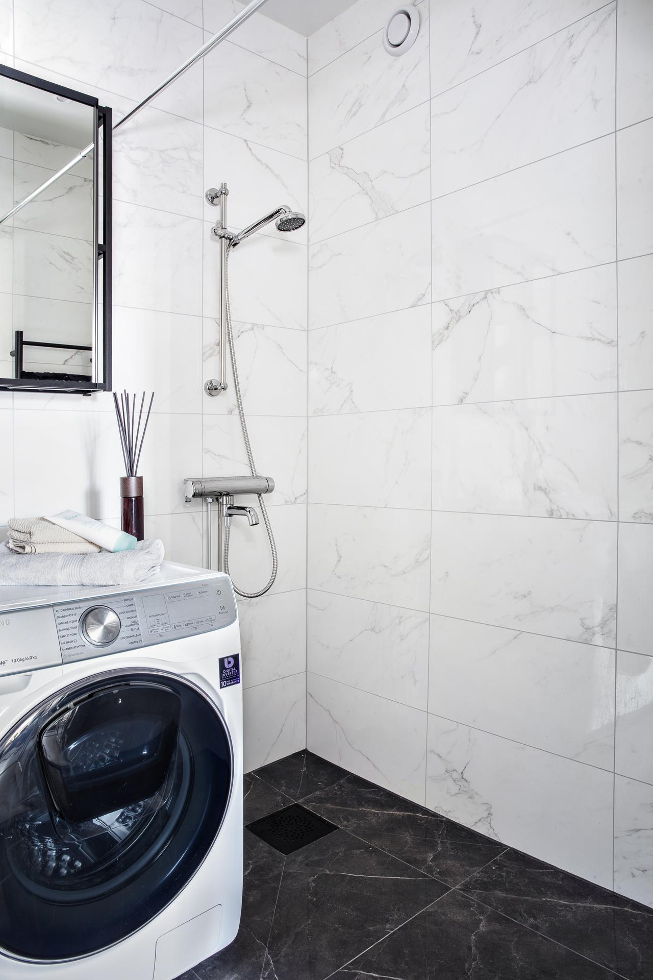 Här finns en duschhörna och en kombinerad tvätt- /torkmaskin