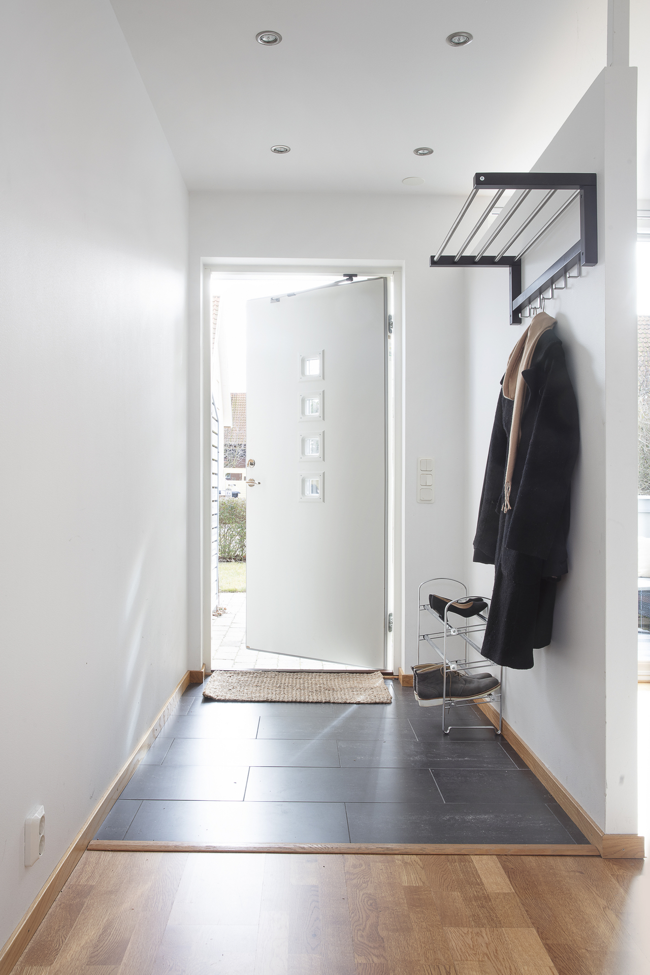 Entré med klinkers på golvet och integrerade spotlights i taket samt plats för avhägning på vänster sida
