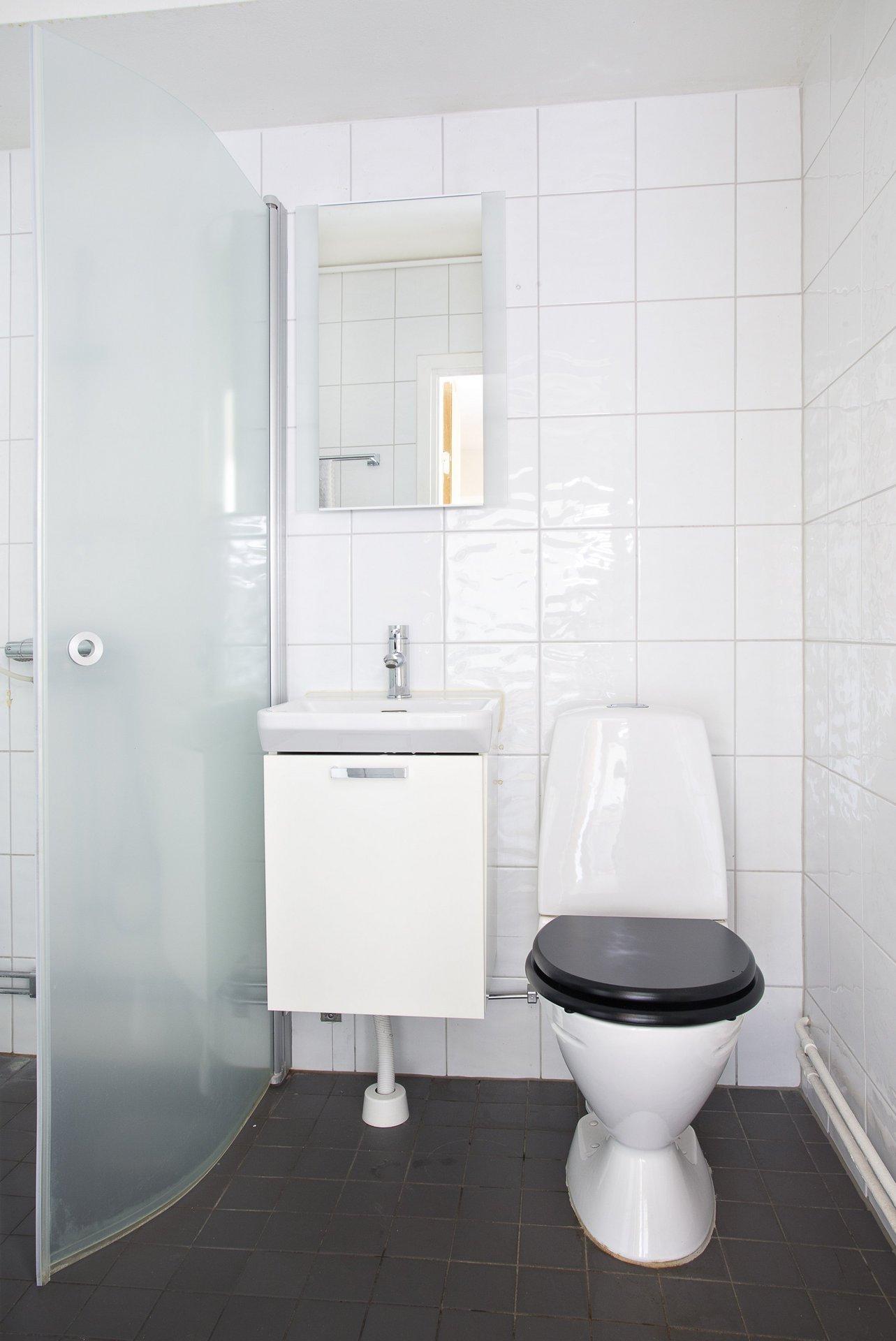 Det helkaklade badrummet har dusch bakom vikväggar